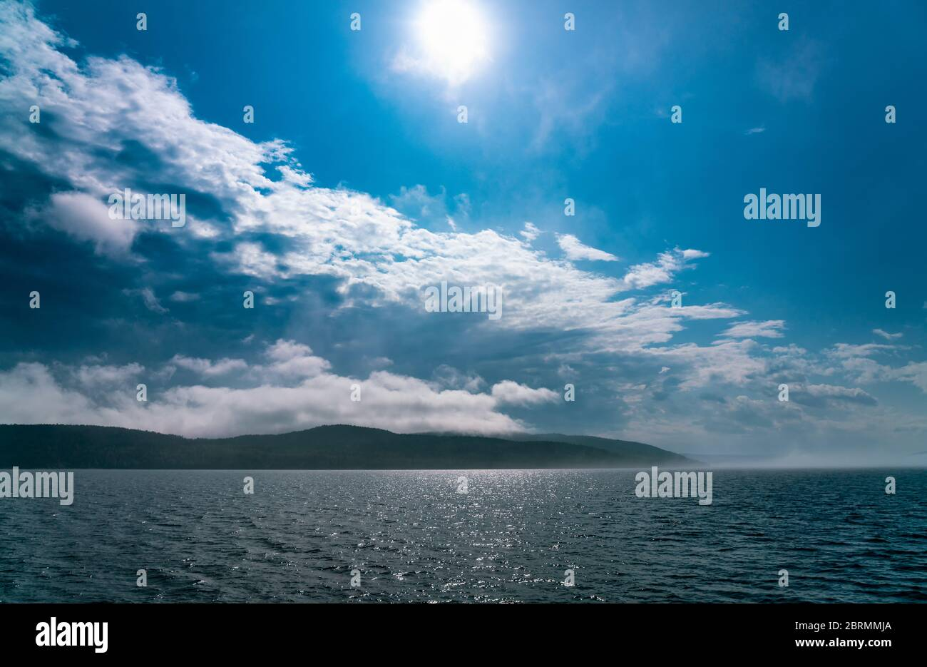 La niebla marina que se depositan sobre el mar desaparece bajo el fuerte sol de la mañana, casi ningún viento, cielos azules Foto de stock