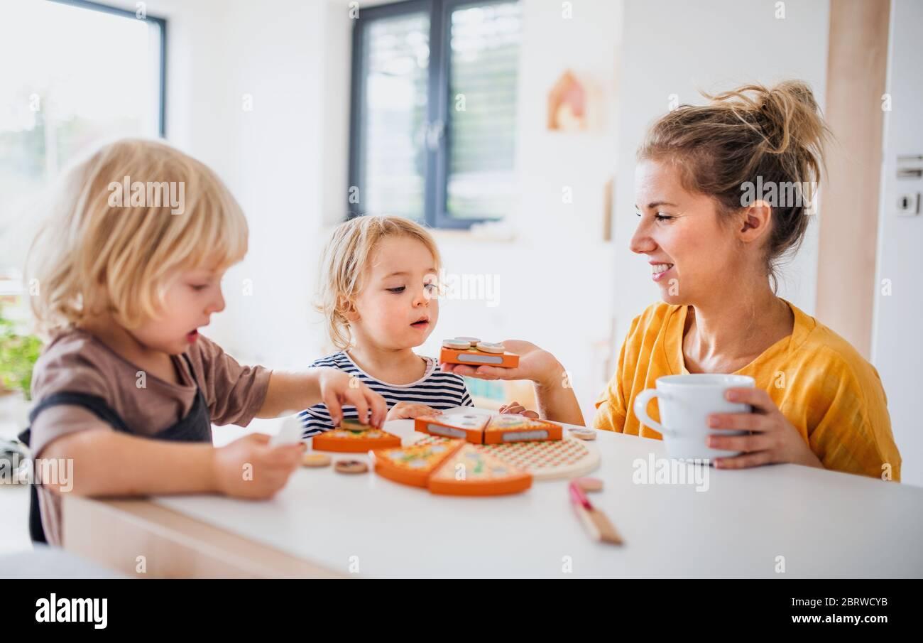Madre con dos niños pequeños en el interior en el dormitorio jugando con juguetes. Foto de stock