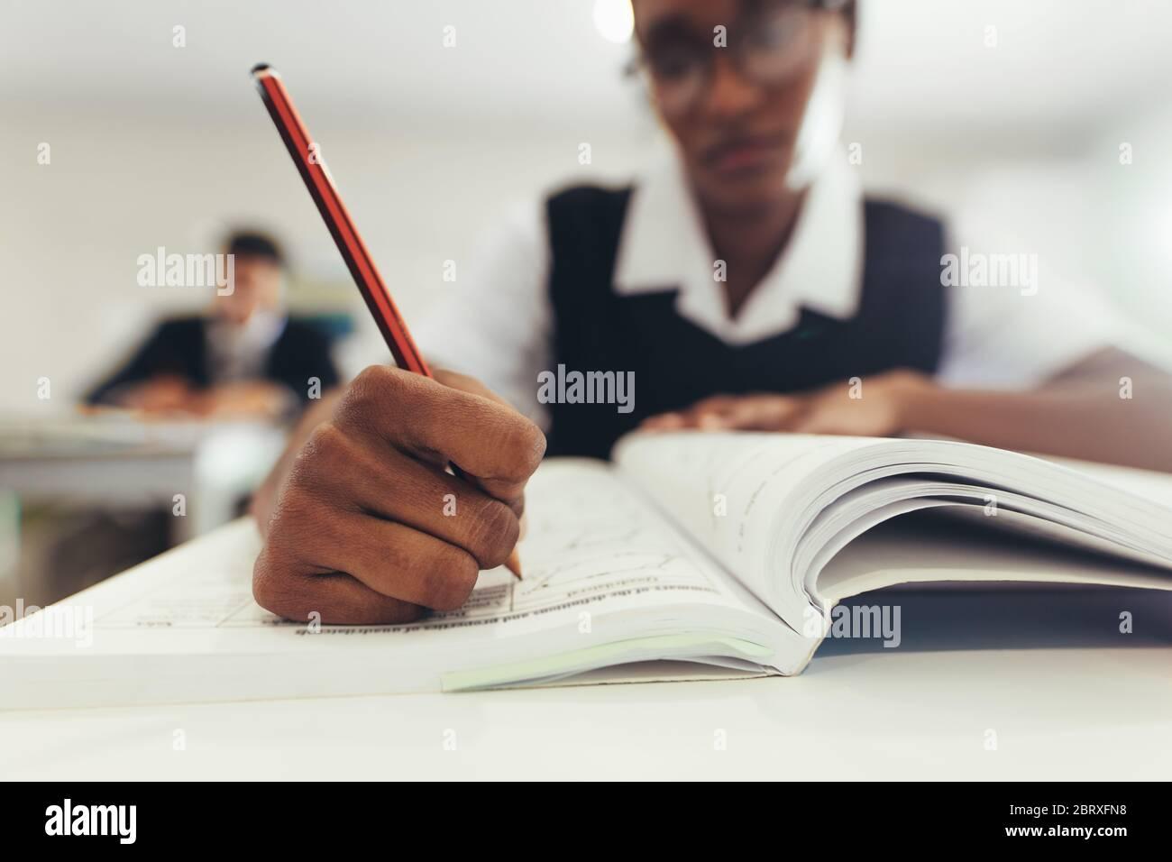 Primer plano de una adolescente escribiendo en su libro de texto mientras se sentaba en el escritorio en el aula. Estudiante de secundaria concentrándose mientras escribe en un libro, focu Foto de stock