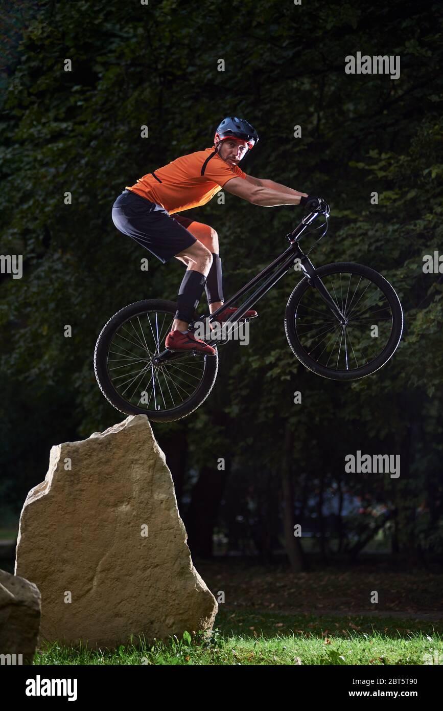 Vista frontal de un ciclista mirando a la cámara durante un salto alto en una bicicleta. Atleta manteniendo el equilibrio en la rueda trasera de la bicicleta de montaña. Concepto de estilo de vida activo. Foto de stock
