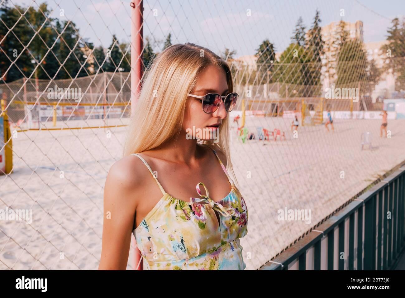 Retrato De Una Chica Rubia Bonita Esta De Pie Delante De Un Campo De Deportes Playa Ella Esta Usando Un Vestido De Verano Corto Y Gafas De Sol Fotografia De Stock