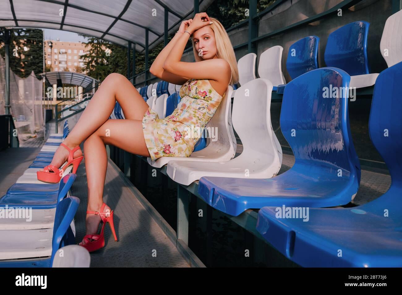 Una chica rubia bonita está sentada en un stand (tribuna). Lleva un vestido corto y tacones altos rojos. Es soleado. Foto de stock
