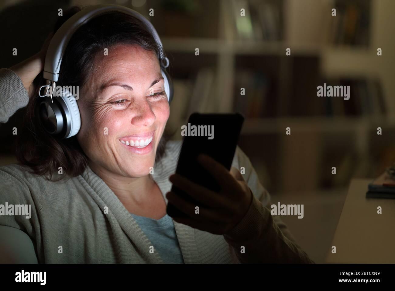 Feliz mujer adulta con auriculares escucha música en el teléfono inteligente con pantalla iluminada en el salón por la noche en casa Foto de stock
