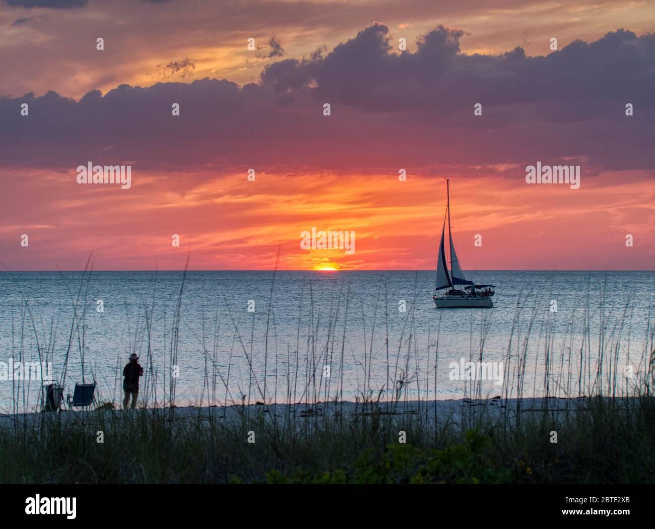 Velero en el Golfo de México al atardecer con un cielo naranja en la playa Nokomis en la costa del Golfo de Florida Foto de stock