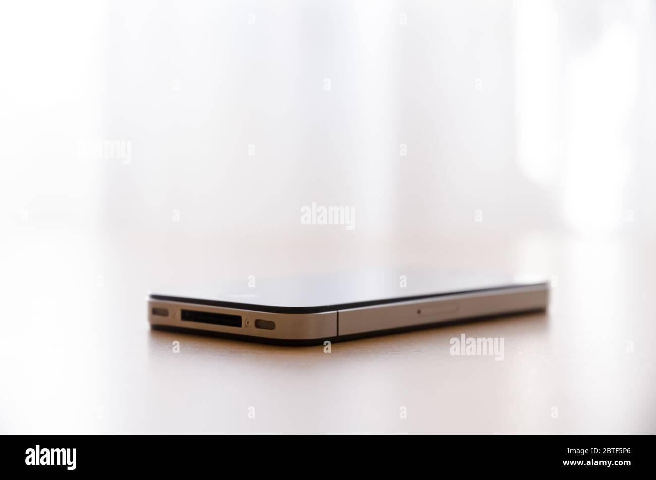 Primer plano de teléfono, teléfono celular iPhone 4s smartphone en un escritorio de madera en un entorno de oficina Foto de stock