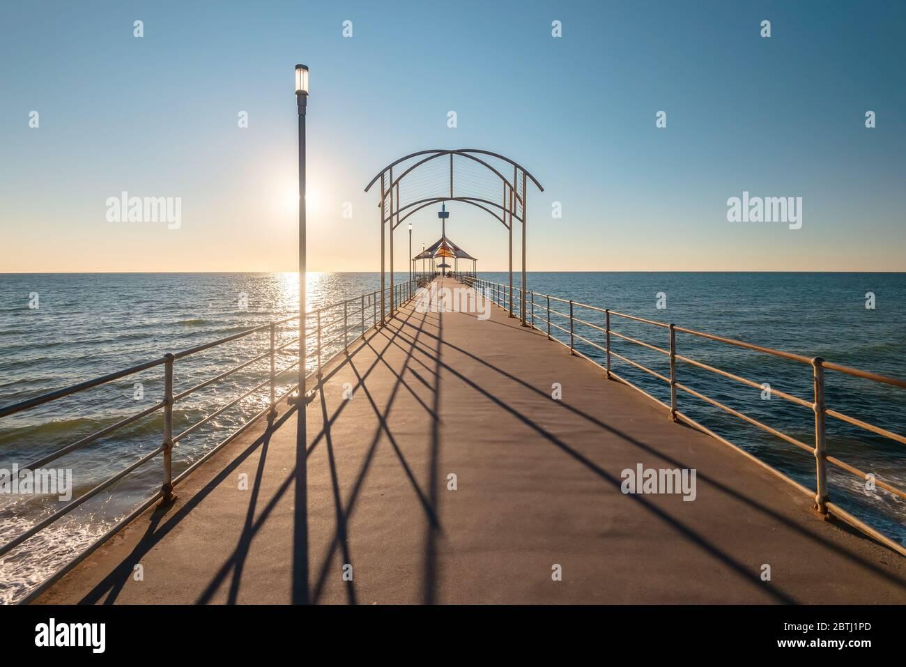El emblemático Brighton Jetty al atardecer con cielo azul, Australia Meridional Foto de stock