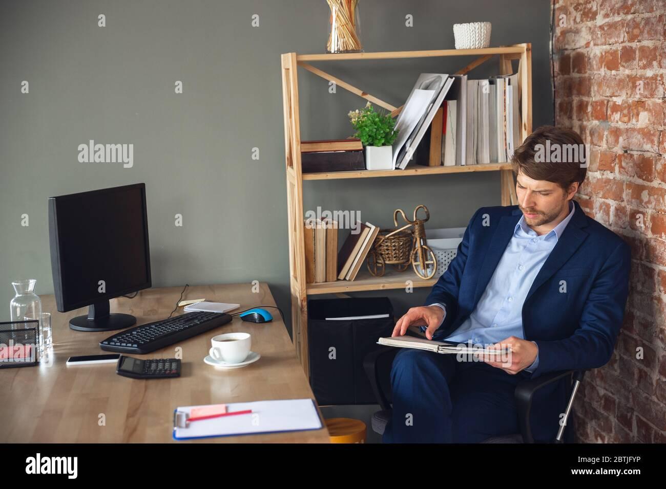 Revisar documentos, tareas, papeleo. Joven, gerente vuelve a trabajar en su oficina después de la cuarentena, se siente feliz e inspirado. Volviendo a la vida normal. Negocio, finanzas, concepto de emociones. Foto de stock