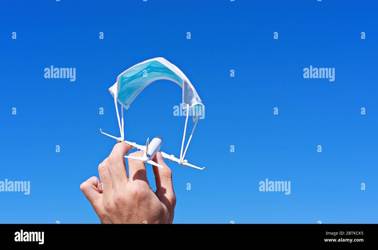 Avión en mano masculina con paracaídas de cara mascarilla quirúrgica contra el cielo azul. Nuevas normas seguras en cabina de aeronaves. Prohibición de vuelos es concepto suspendido, espacio de copia Foto de stock
