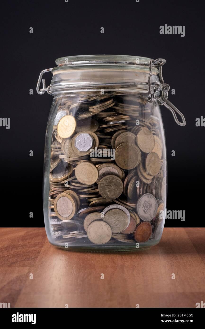 Monedas dentro de un recipiente de vidrio lleno de dinero Foto de stock