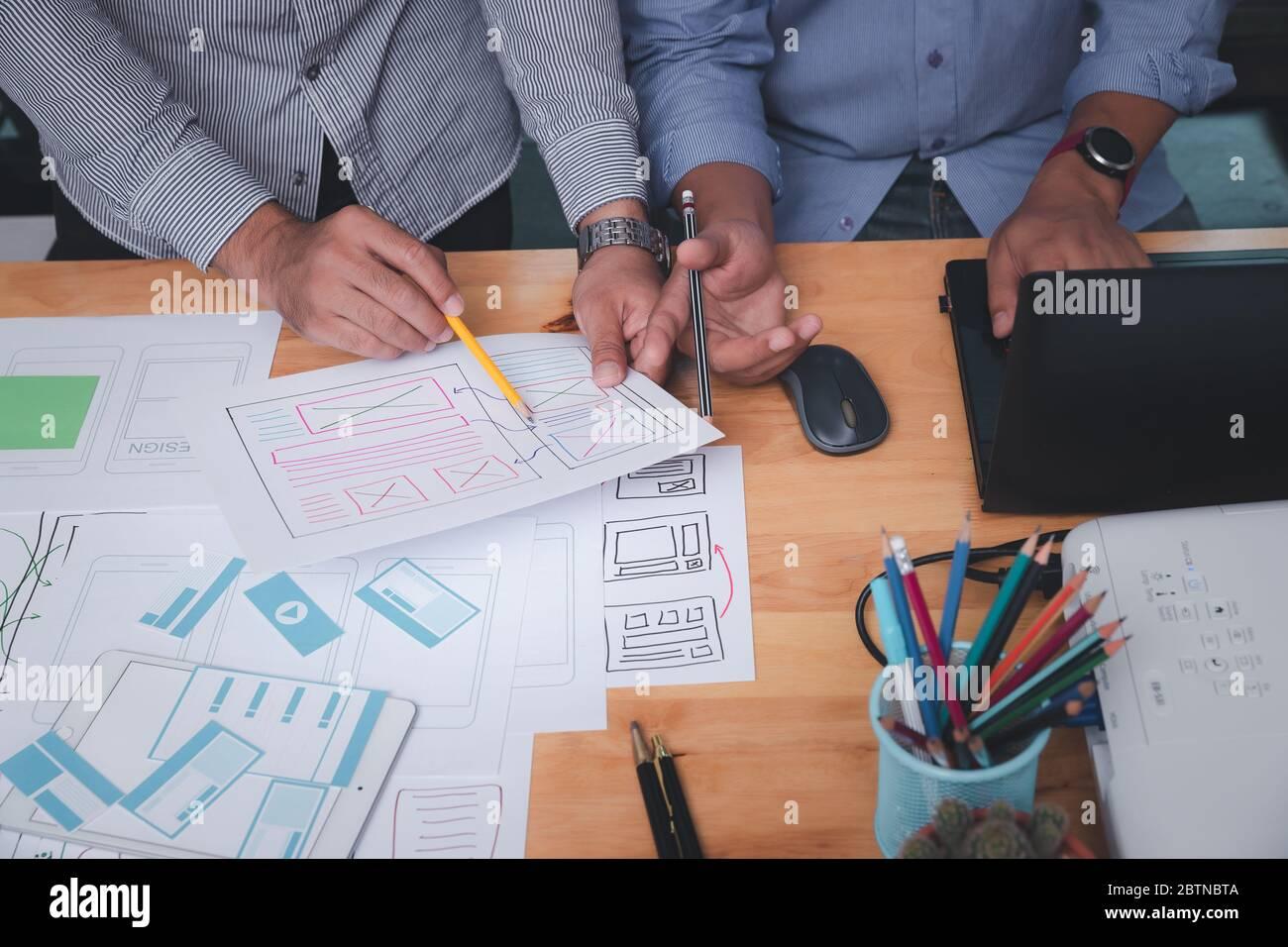 Diseñadores de UX o UI que diseñan en su proyecto prototipo de diseño de aplicaciones para smartphones. Foto de stock