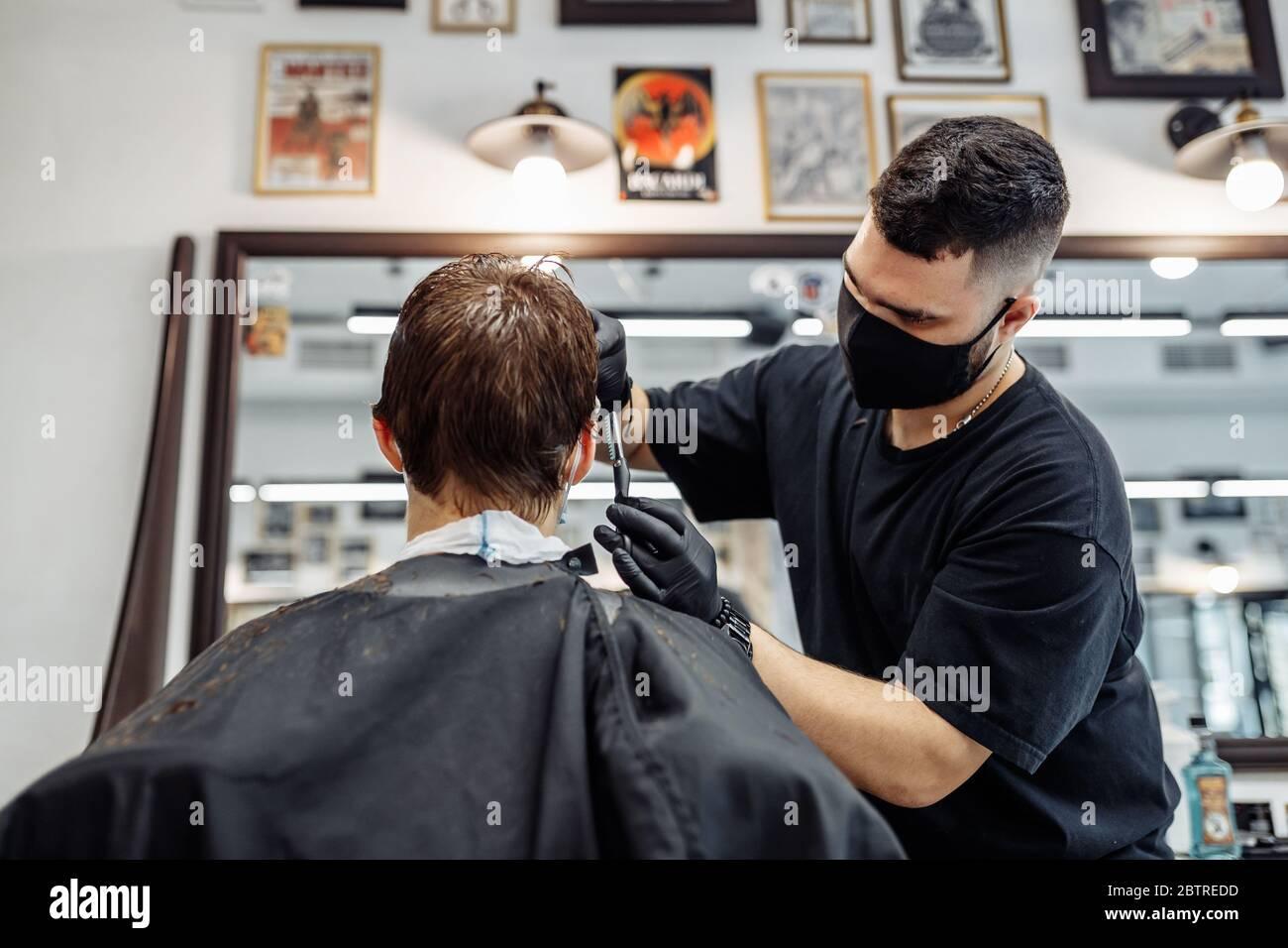 Adelgazamiento y peinado del cabello. Peluquería hace un corte de pelo al cliente. Foto de stock