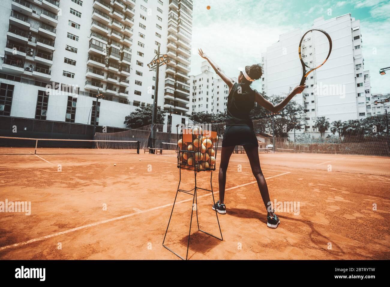 Vista gran angular desde detrás de una joven mujer biroquial delgada apuntando un golpe antes de golpear una pelota de tenis durante un entrenamiento deportivo o calentamiento en un exterior Foto de stock