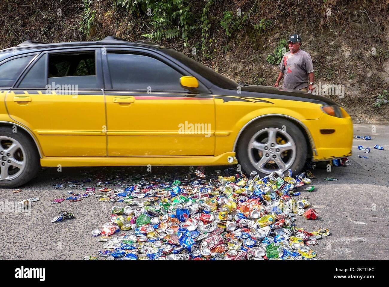 En San Andrés Semetabaj, municipio de Sololá, Guatemala, Alirio López, de 63 años, coloca latas de soda en una carretera para que los coches que pasan los aplasten. Alirio recicla las latas en utensilios de cocina. (Brenda Leticia Saloj Chiyal, GpJ Guatemala) Foto de stock
