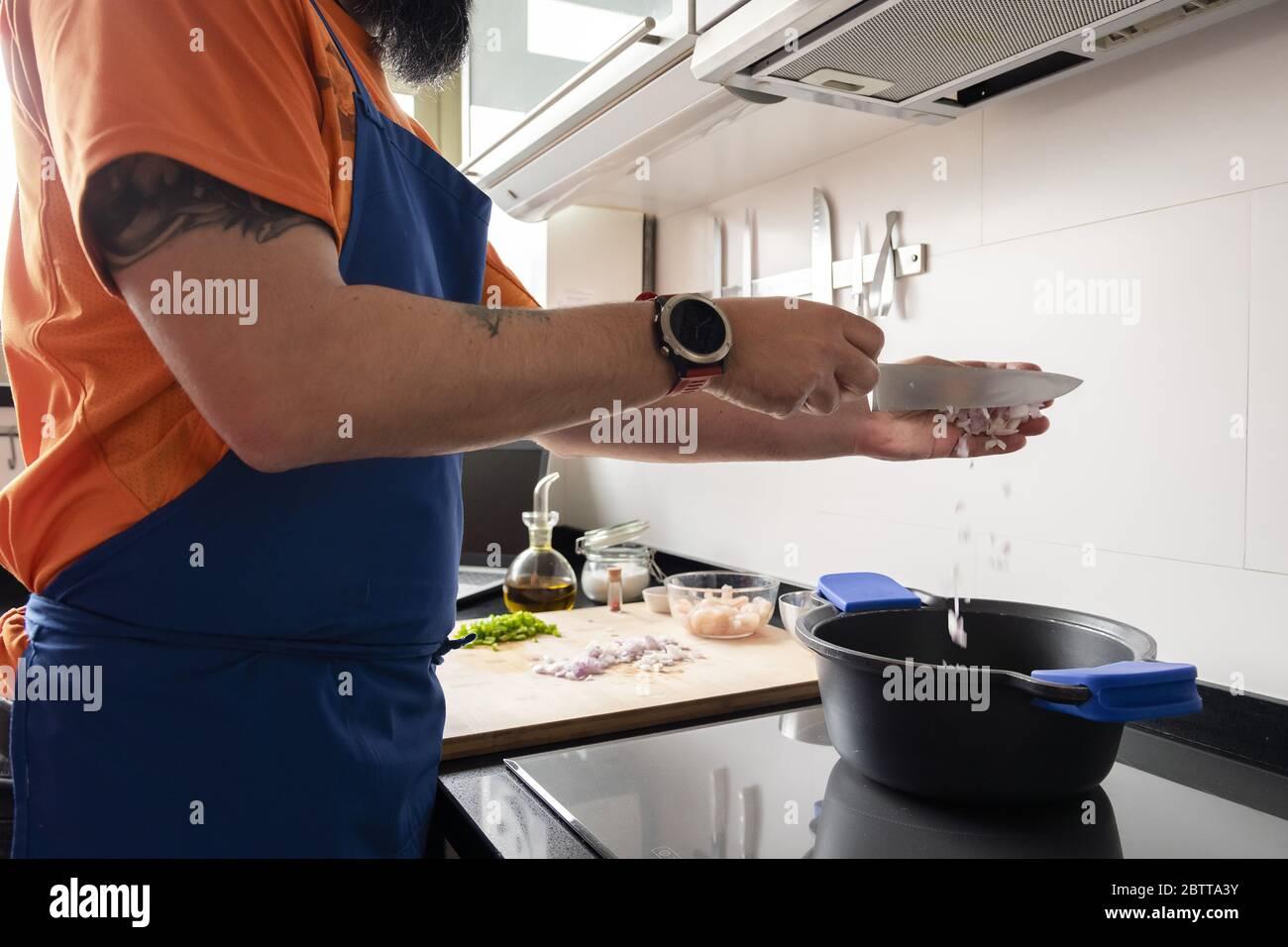 hombre irreconocible poniendo cebolla picada en una olla para preparar una comida saludable, concepto de cocina casera Foto de stock