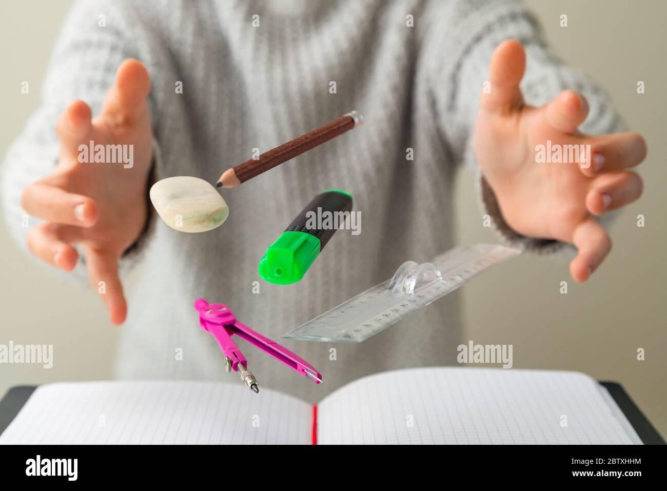 Levitando materiales escolares para matemáticas - cuaderno, pluma, regla, lápiz, divisor y borrador levitando entre las manos de los estudiantes. Concepto de educación y crea Foto de stock