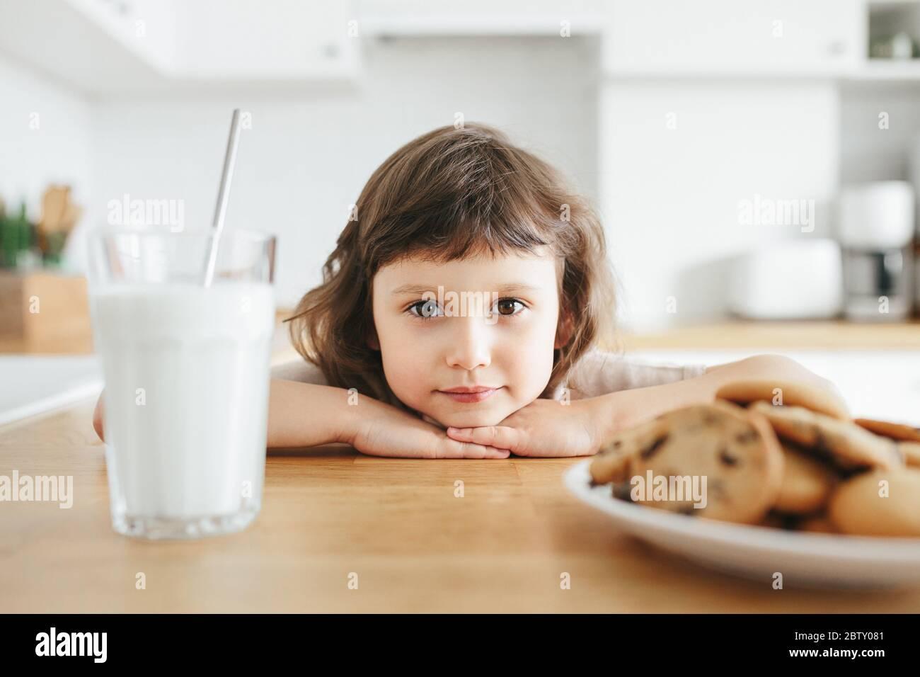 Linda niña pequeña bebiendo leche con paja de acero de vidrio y comiendo galletas sentadas en la mesa de la cocina. Reduzca el uso de plástico en casa con los niños Foto de stock