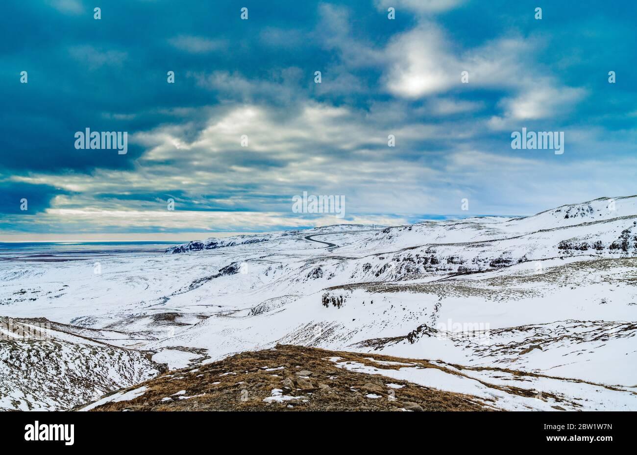 Nubes dramáticas sobre el paisaje de montaña cubierto de nieve con camino adentro el fondo Foto de stock