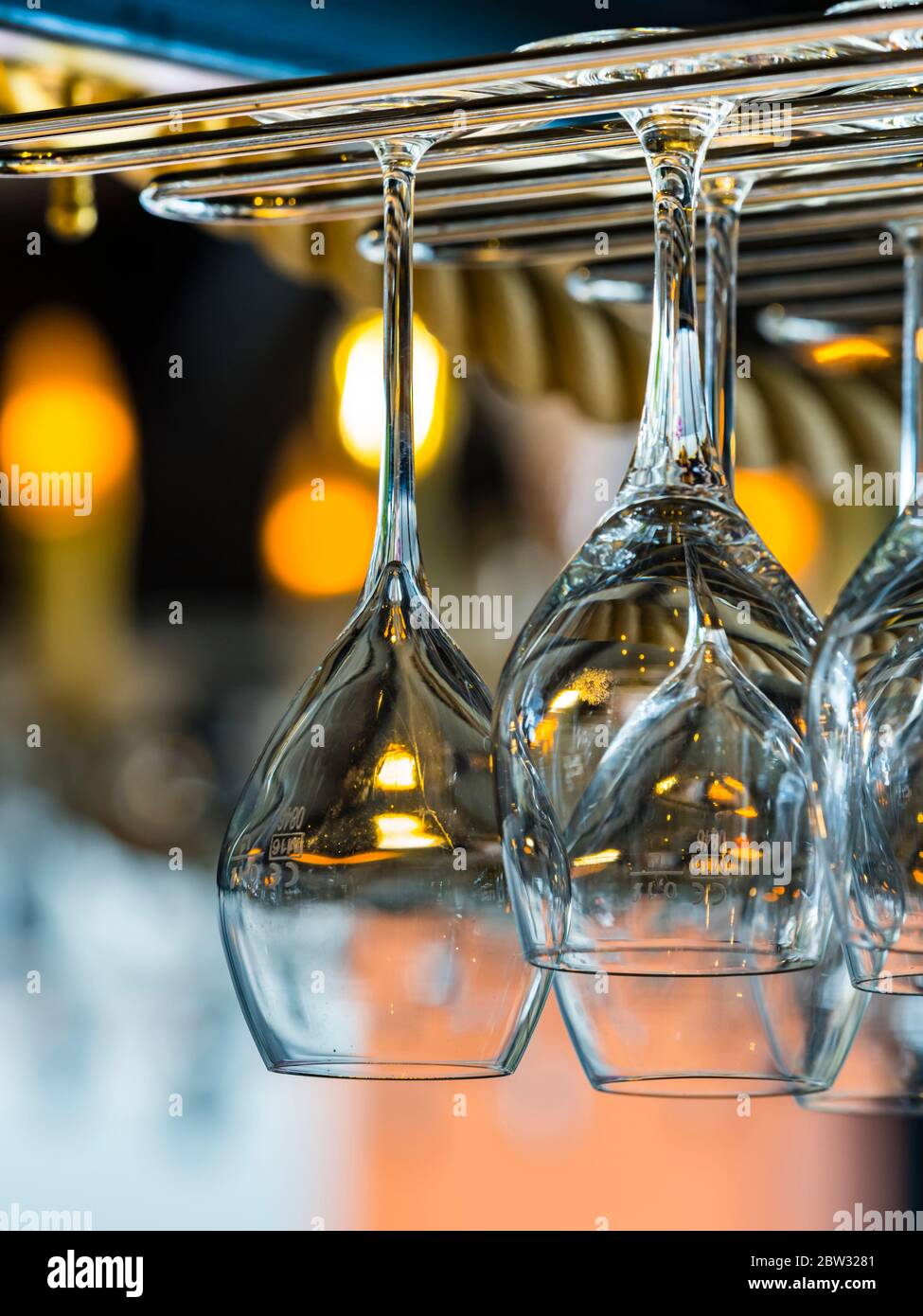 Muchos manojo múltiple de vasos vacíos listos limpios lavados limpios colgados por encima invertidos en la barra aislada Foto de stock