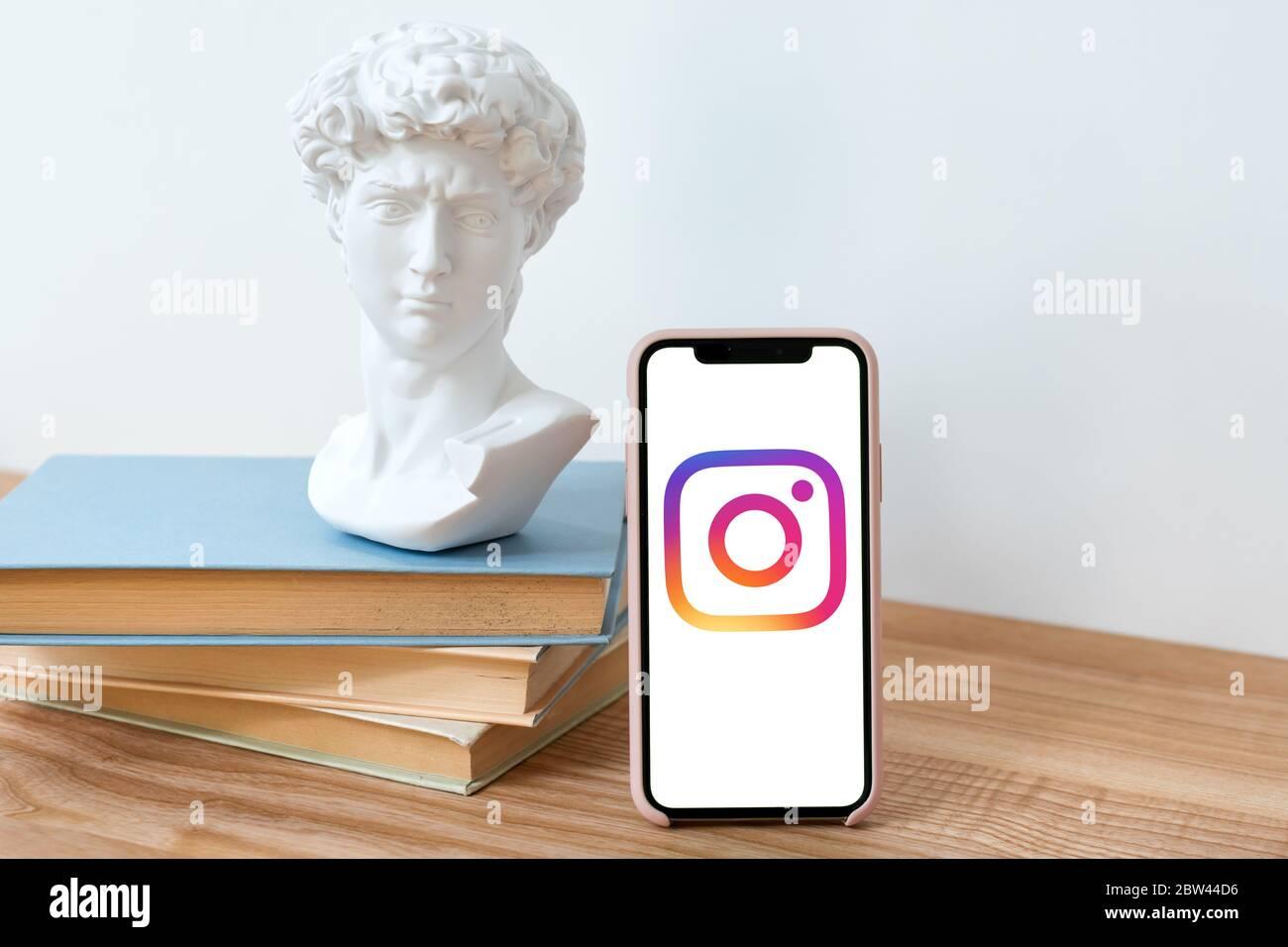 Kiev, Ucrania - 28 de mayo de 2020: Logotipo Instagram en iPhone X pantalla en mesa de madera con libros y David busto estatua. Red de redes sociales. Foto de stock