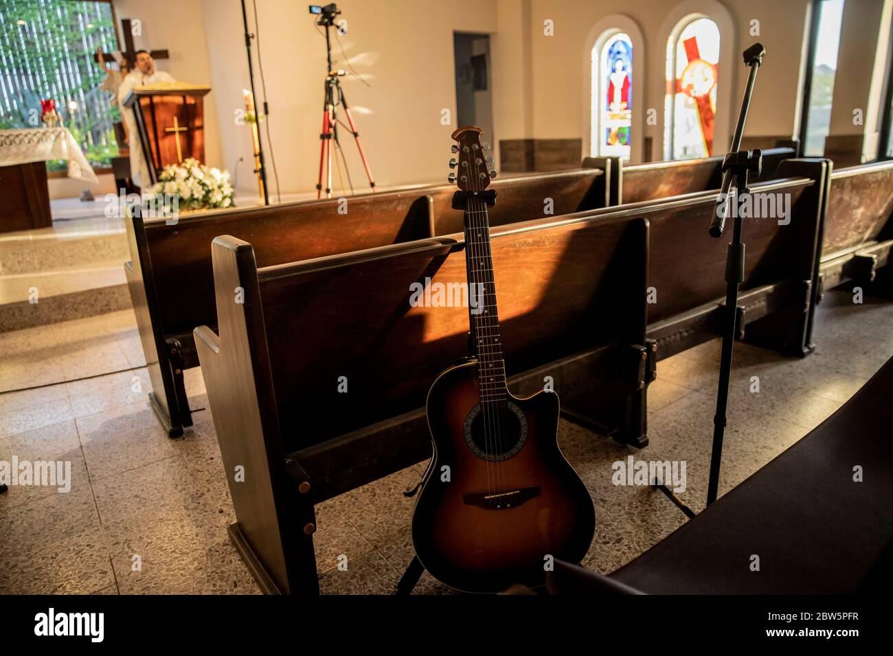 """HERMOSILLO, MÉXICO - MAYO 27: Una guitarra está sola en un espacio donde el coro del templo de Santa María de Guadalupe suele cantar, ya que el inicio de la masa pandémica se ha mantenido a puerta cerrada a través de redes sociales, como parte de la saludable perturbación de Covid-19 el 27 de mayo de 2020 en Hermosillo, México. A pesar del creciente número de casos positivos de COVID-19 en el país, el programa """"distancia saludable"""" finaliza el 31 de mayo, pero las restricciones continuarán en aquellas ciudades con un elevado número de casos confirmados. (Foto de Luis Gutiérrez/ Norte Foto) Foto de stock"""