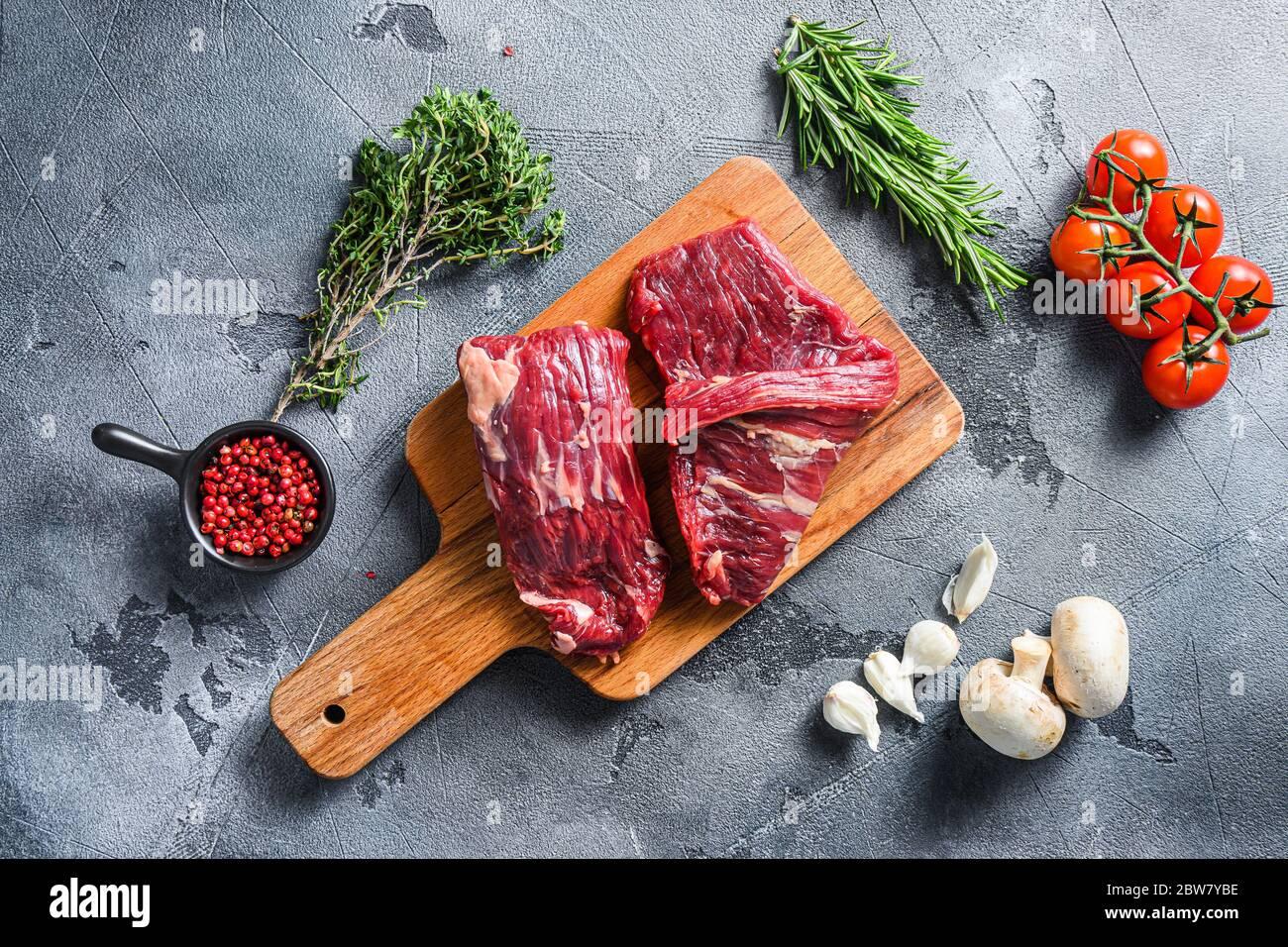 Filete de solapa crudo corte flanco con Machete, Falda Steak, en madera tabla de cortar, con hierbas tomates peppercorns sobre piedra gris superficie fondo vi Foto de stock