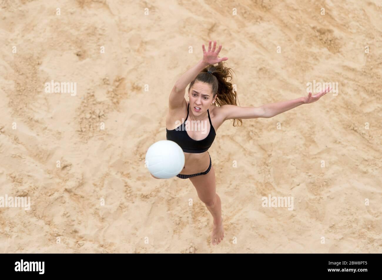 Mujer joven con pelota blanca jugando voleibol en la playa. Vacaciones de verano y concepto deportivo Foto de stock