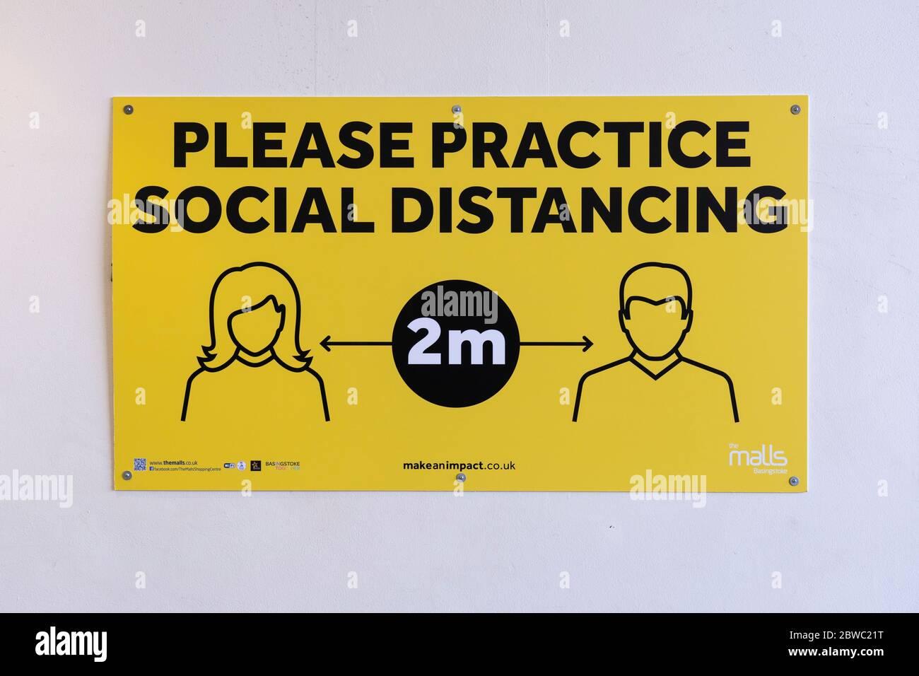 Un cartel en el centro de la ciudad de Basingstoke, solicitando que la gente practique distanciamiento social y mantenga una distancia de 2 m durante la pandemia del Covid 19 Coronavirus, Reino Unido Foto de stock