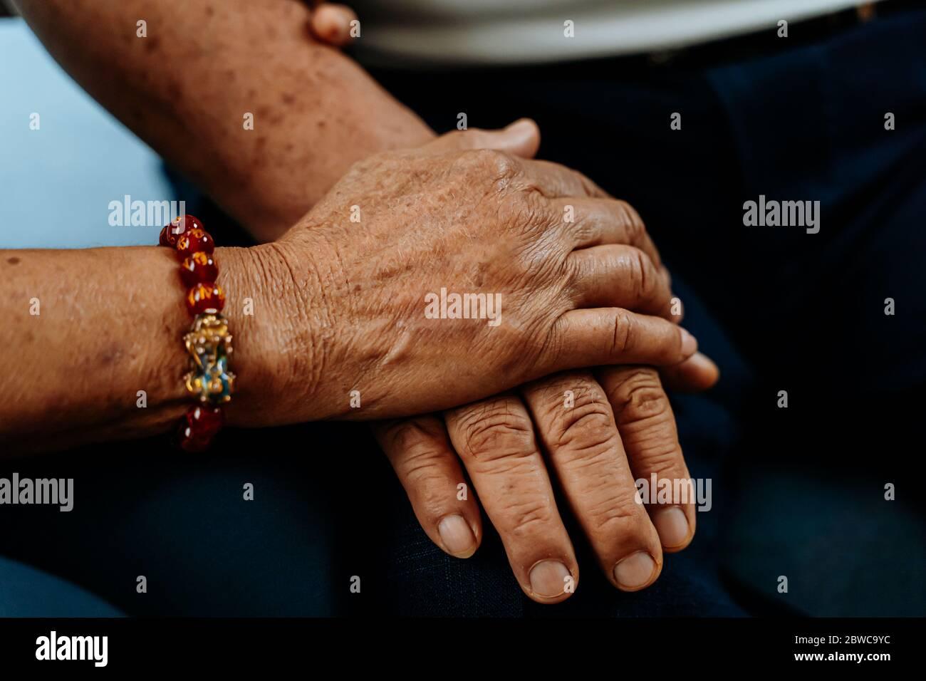 Cerca de la mano de una anciana que sostiene las manos de un anciano. Concepto de amor romántico duradero para siempre Foto de stock