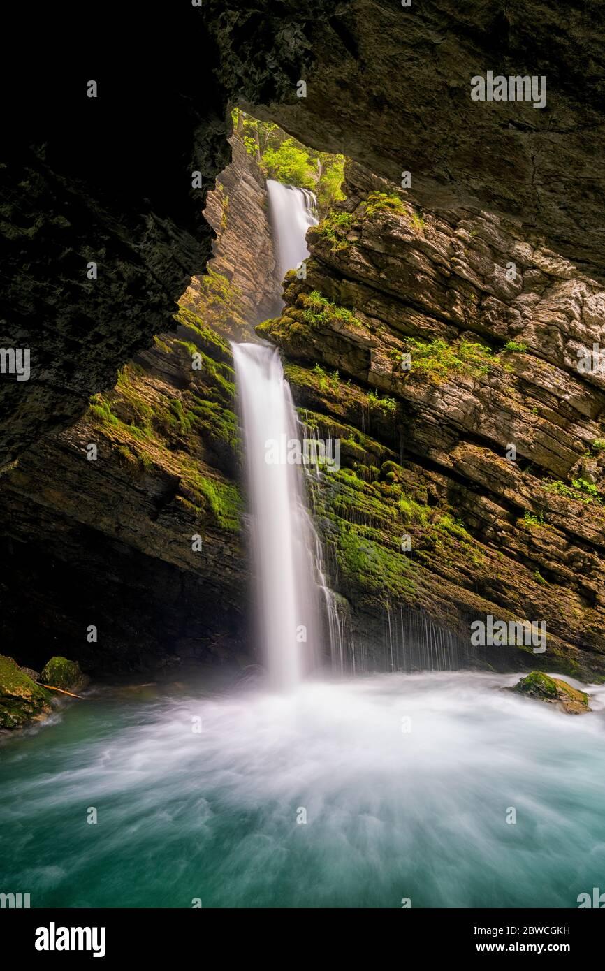 Una vista de una idílica cascada en el exuberante paisaje de follaje de primavera verde en los Alpes suizos Foto de stock