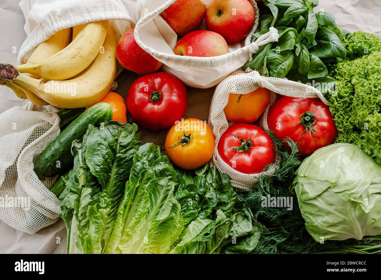 Verduras frescas y frutas en bolsas reutilizables de algodón ecológico en la mesa en la cocina. Vida sostenible Foto de stock