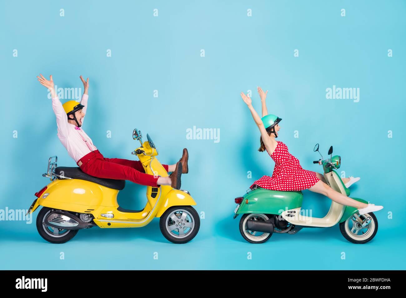 Foto de perfil de tamaño completo de la señora tonta pareja de dos viajeros en ciclomotor retro fácil manera de separar piernas montar sin brazos con ropa vintage divertido Foto de stock