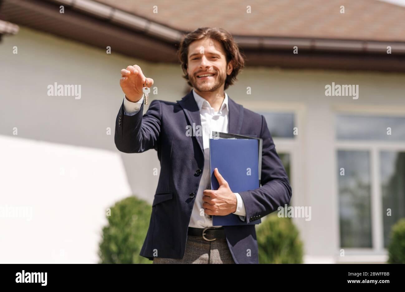 Sonriente agente inmobiliario sosteniendo la llave de la casa cerca de la nueva residencia a la venta, al aire libre Foto de stock