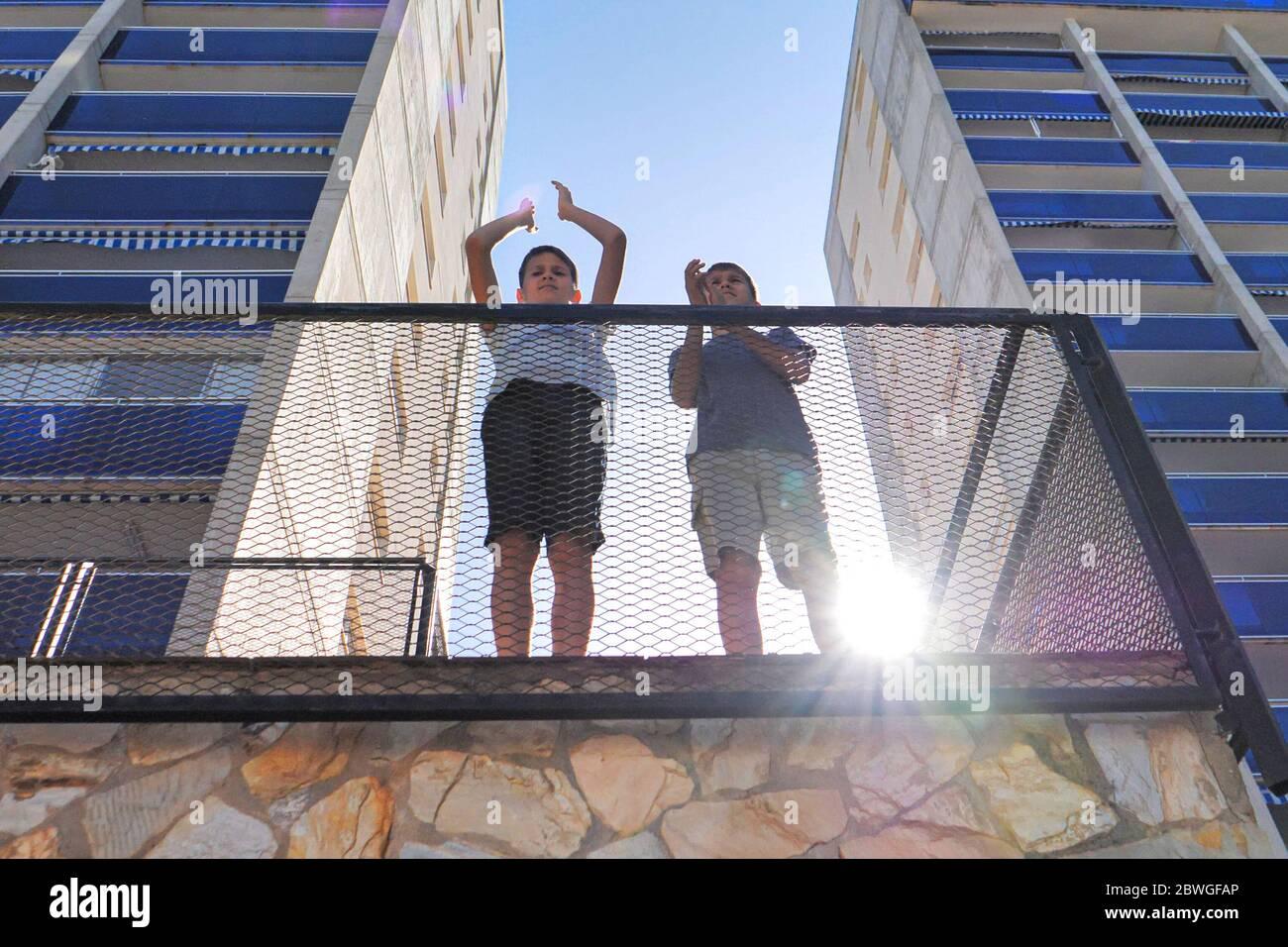 Los niños se palman, aplaudiendo desde el balcón de la terraza para apoyar a los médicos, enfermeras, trabajadores del hospital durante la cuarentena pandémica del Coronavirus Covid-19 Foto de stock