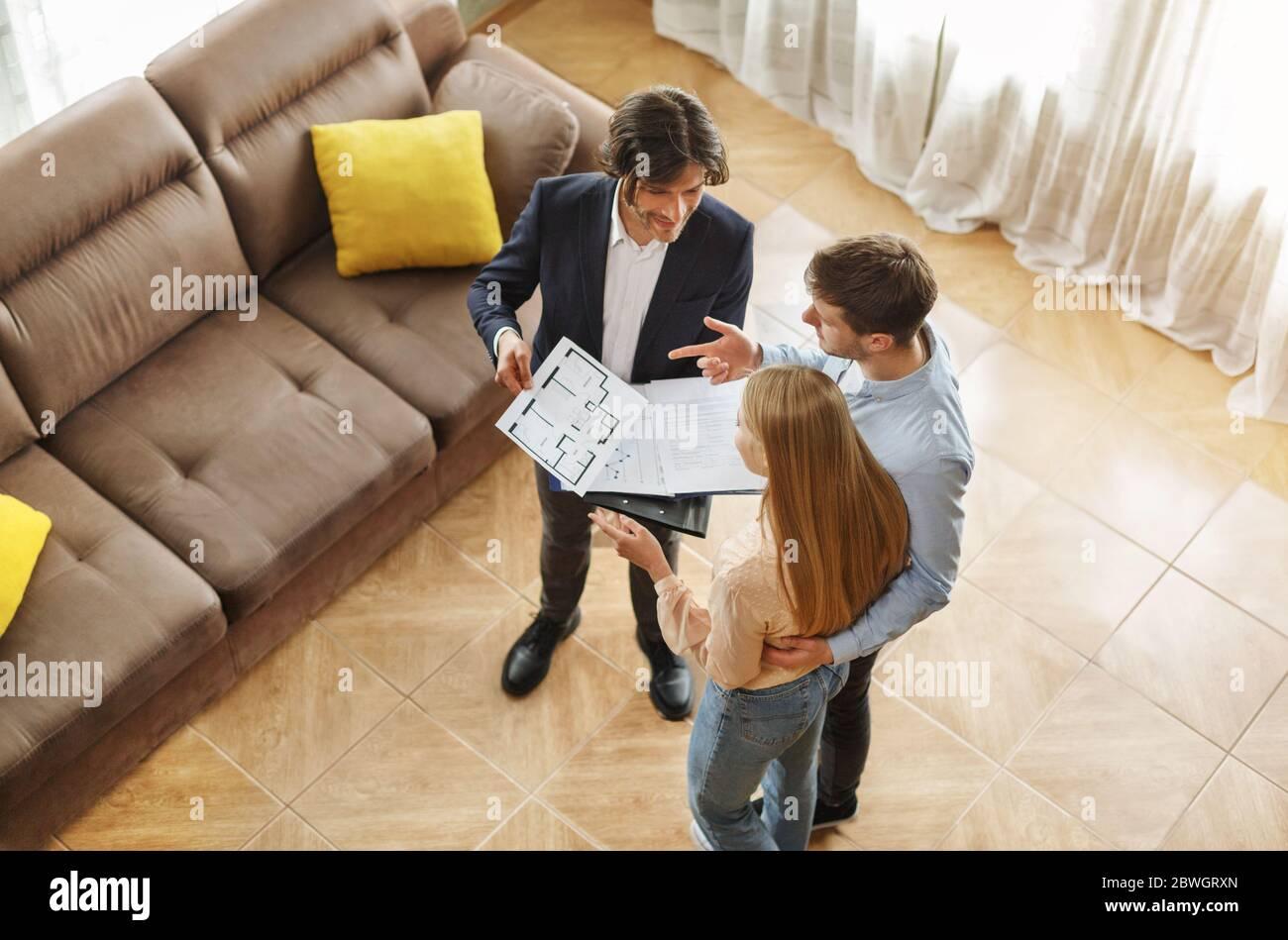 Vista superior de agente inmobiliario comunicándose con clientes sobre la compra de casa o alquiler de interiores Foto de stock