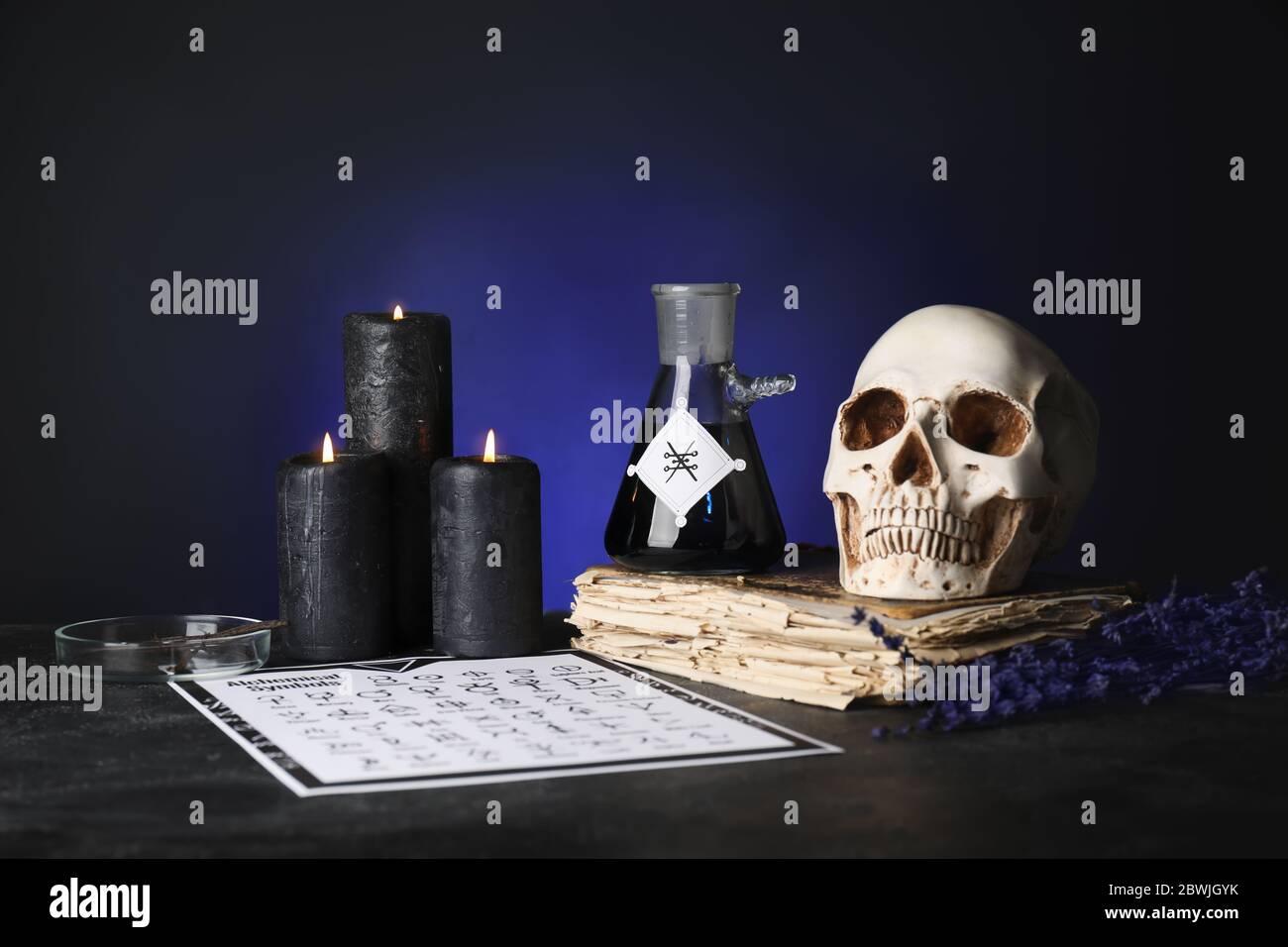 Pociones, cráneo humano y libro viejo en la mesa de alquimista Foto de stock