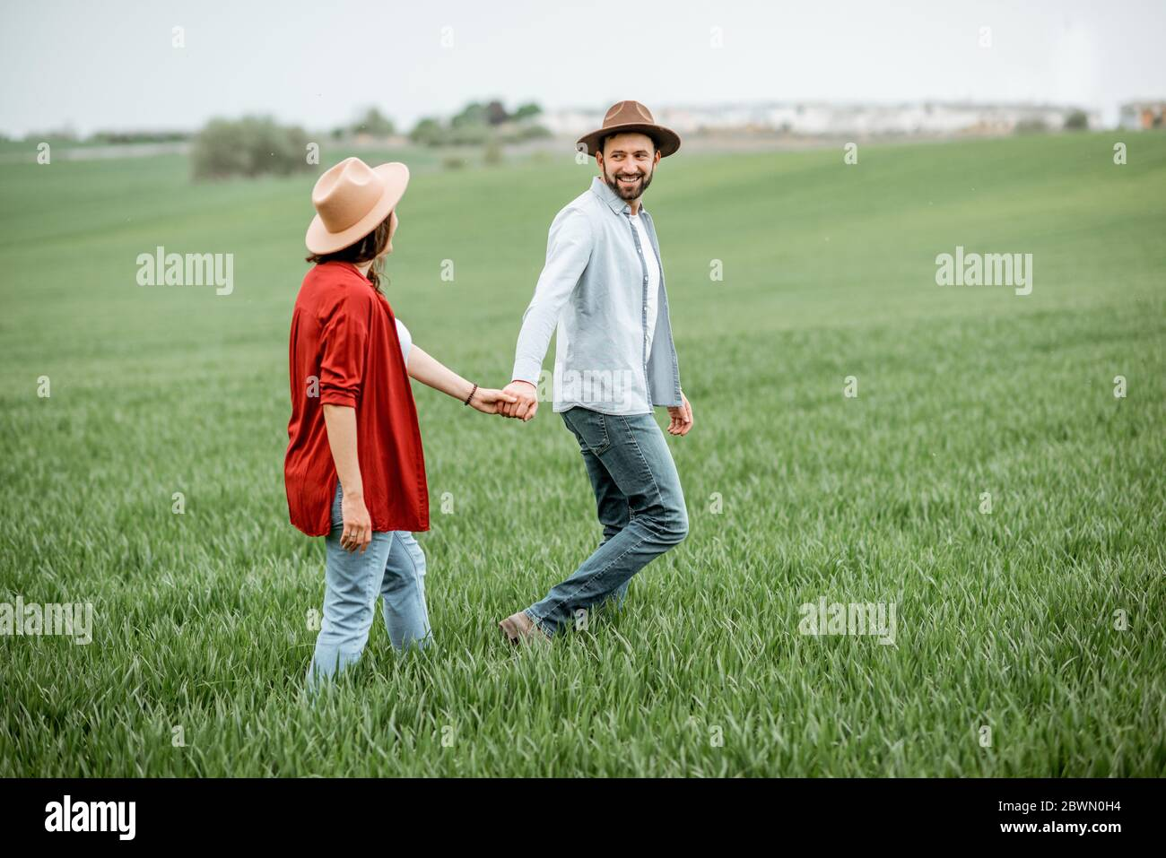 Mujer embarazada con su hombre divirtiéndose juntos, caminando por el campo verde. Feliz pareja esperando un bebé, joven concepto de familia Foto de stock
