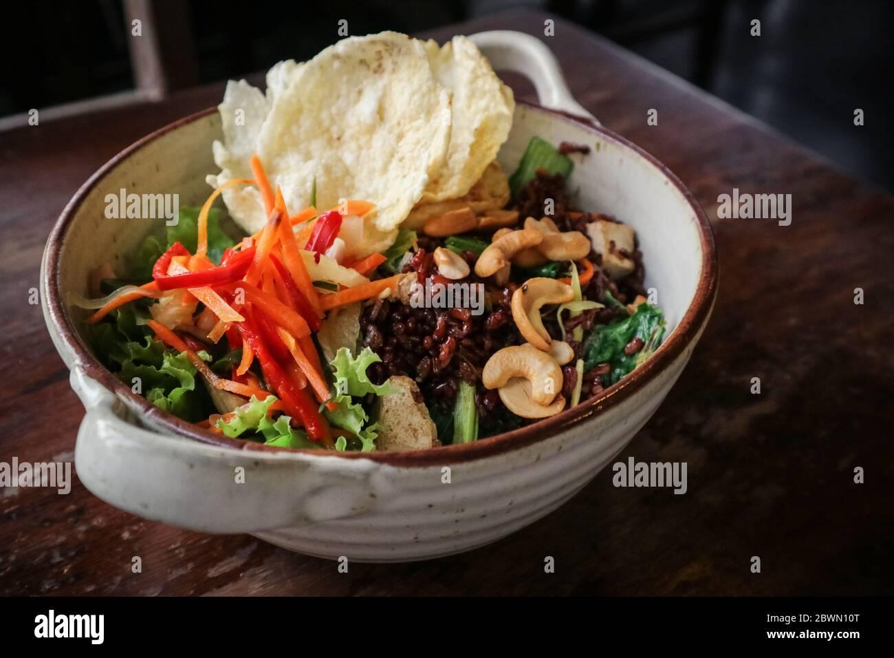Arroz Rojo orgánico Nasi Goreng, arroz frito vegetariano con un montón de verduras, tofu y anacardos tostados en un tazón sobre fondo de madera Foto de stock