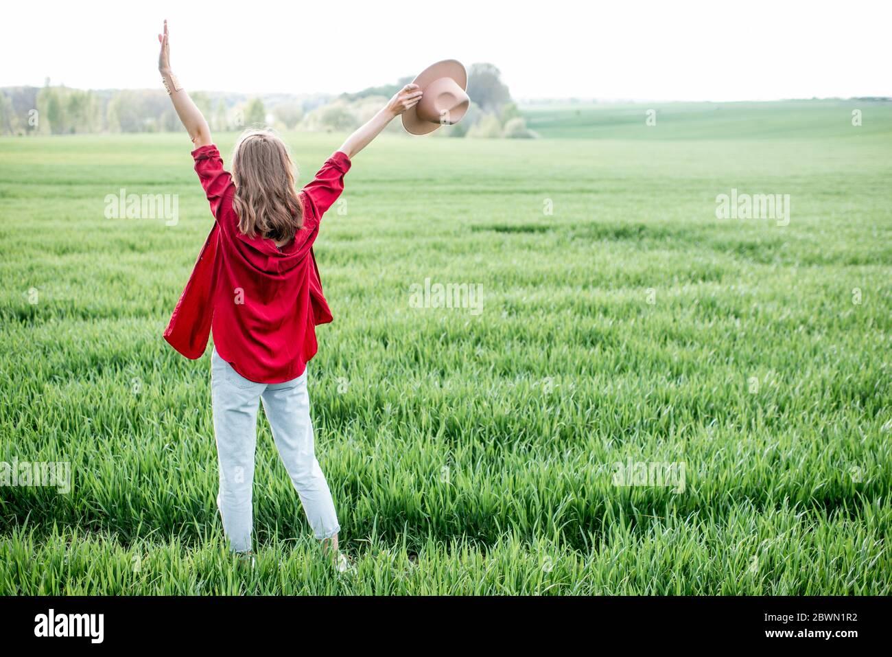 Mujer elegante disfrutando de la primavera y la naturaleza en el campo verde, vista trasera. Concepto de un estilo de vida sin preocupaciones y libertad Foto de stock