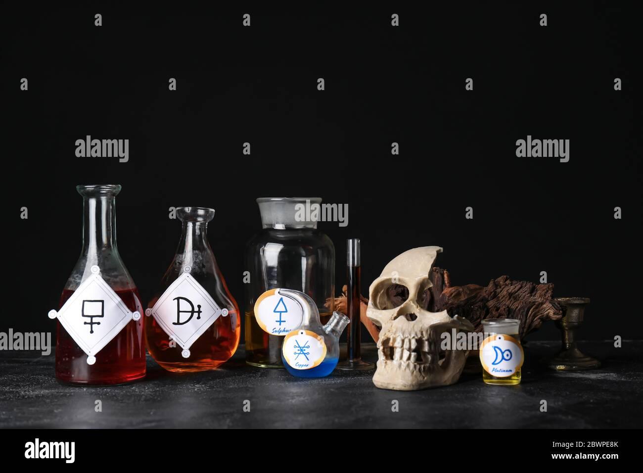 Pociones y cráneo humano en la mesa del alquimista Foto de stock