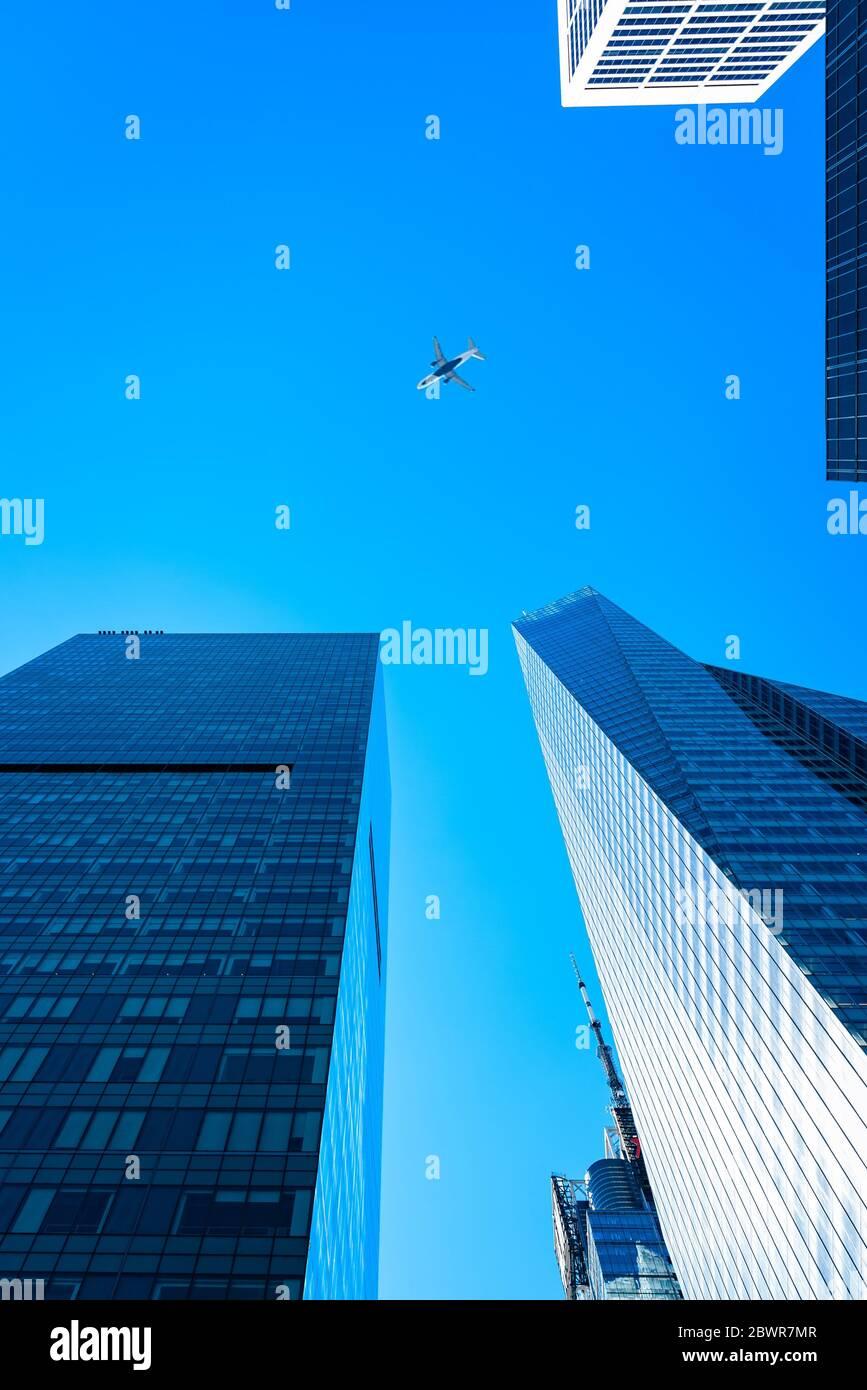 Nueva York, EE.UU. - 20 de junio de 2018: Vista de ángulo bajo de edificios de oficinas modernos y aviones contra el cielo en el centro de Manhattan. Foto de stock