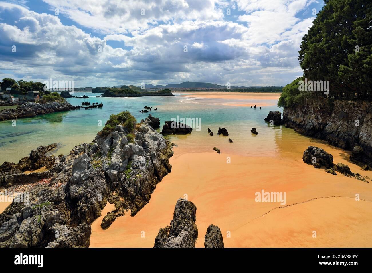 Formaciones rocosas y arena húmeda limpia en la hermosa playa durante la marea baja Foto de stock
