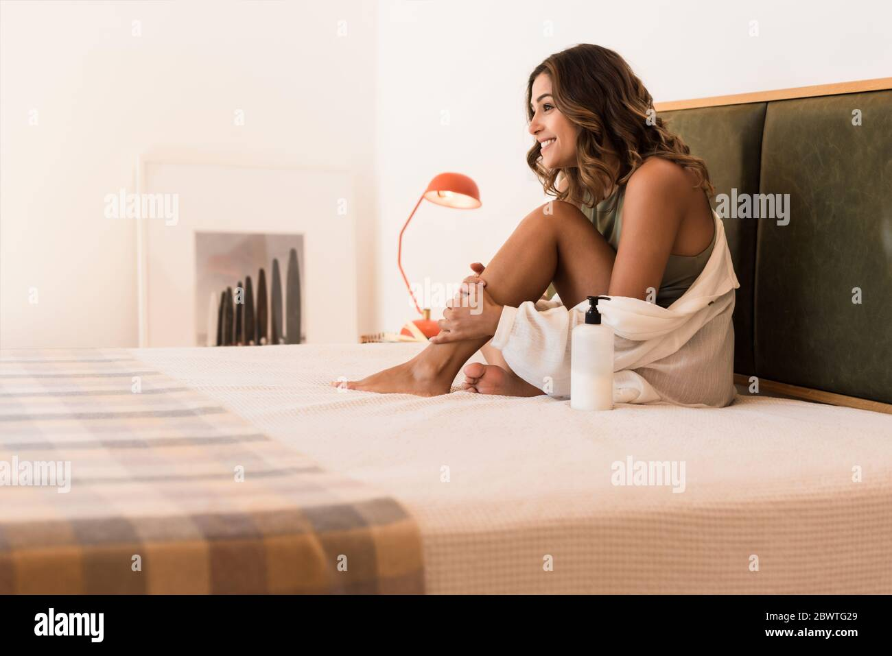 Mujer latina aplicando crema corporal de un recipiente blanco con espacio de copia para calificar Foto de stock