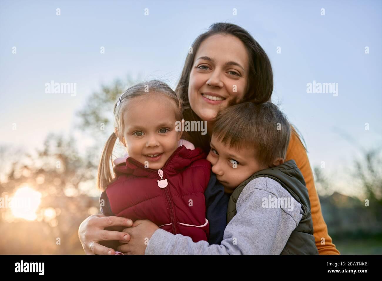 Retrato de madre feliz abrazando a dos niños al aire libre Foto de stock