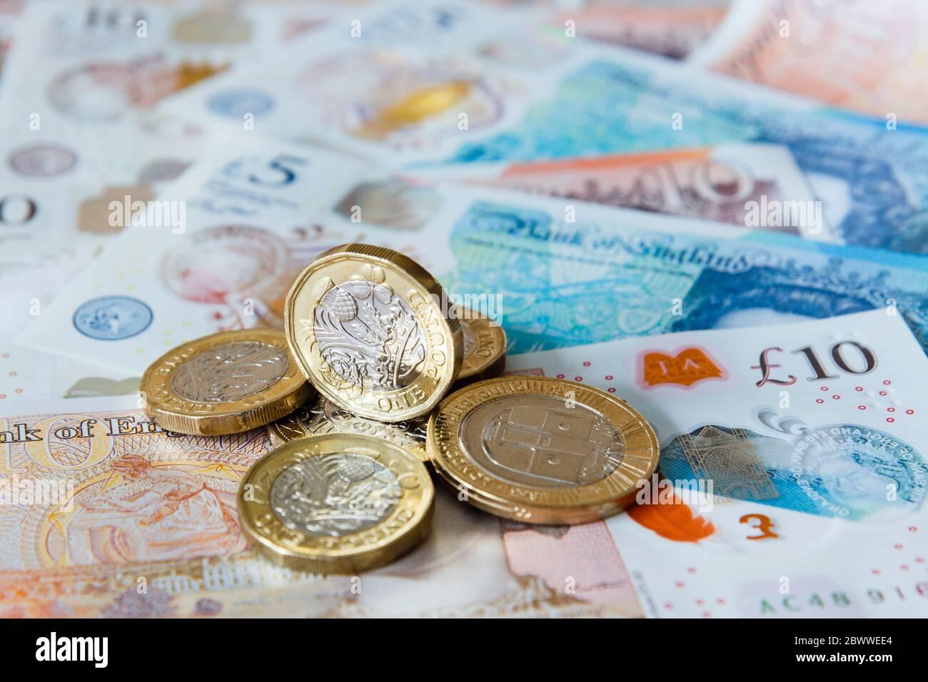 Un montón de una libra de monedas de £ dinero británico libra esterlina en polímero nuevo £ 10 y £ 5 billetes de GBP de primer plano. Inglaterra Reino Unido Gran Bretaña Foto de stock