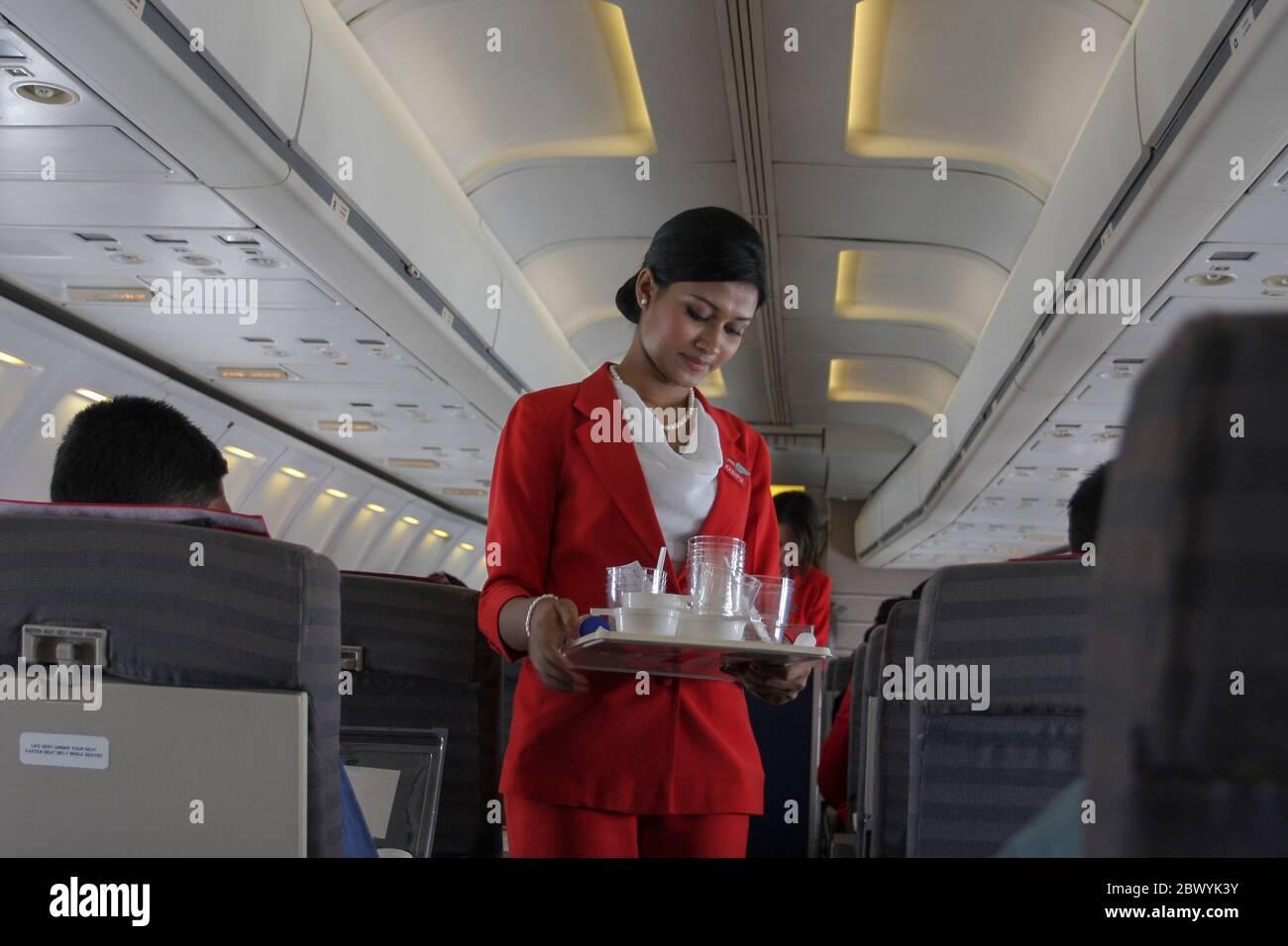Un equipo de cabina recogiendo vidrio de agua usado en un avión de Best Airways. Bangladesh Foto de stock