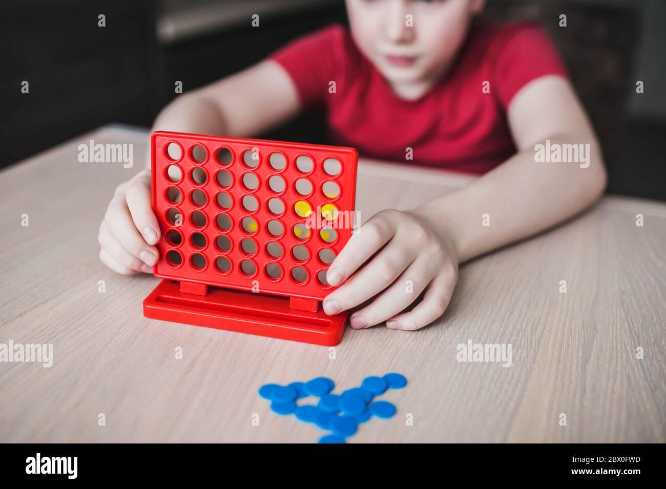 Juego de estrategia de tablero intelectual 'cuatro en una fila' - los niños juegan en la mesa Foto de stock