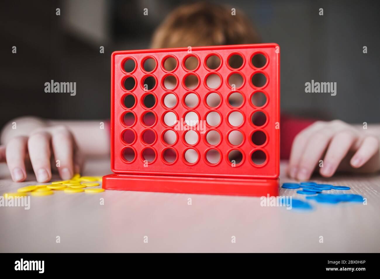 El niño pensó en el movimiento en el juego intelectual lógico de escritorio - el ocio de los niños Foto de stock