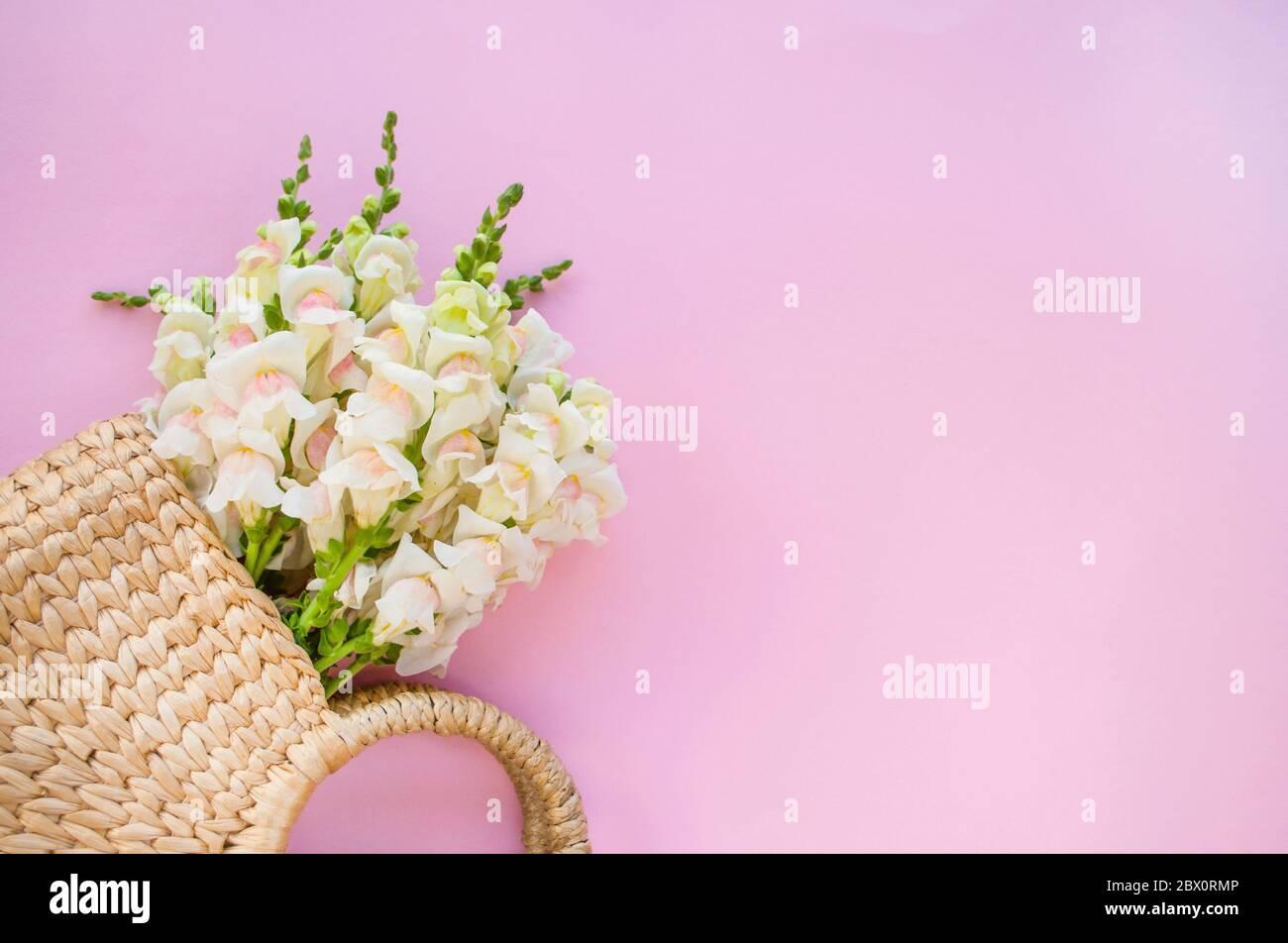 Bolsa de paja moderna con hermoso ramo de flores blancas sobre fondo rosa con copyspace. Foto de stock
