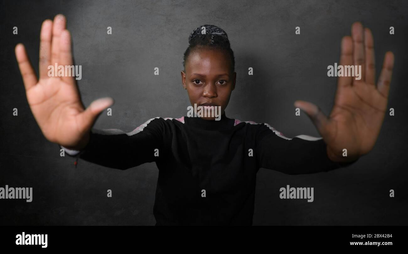 Joven atractiva y segura afro americana en estilo hipster levantando sus brazos y manos en señal de alto exigiendo la paz y detener el racismo abusan de un Foto de stock