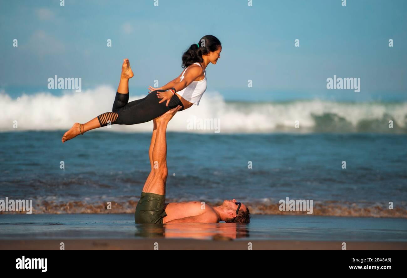 estilo de vida al aire libre retrato joven atractivo y concentrado pareja de acróbatas de yoga practicar el equilibrio de la acroyoga y ejercicio de meditación en la hermosa Foto de stock
